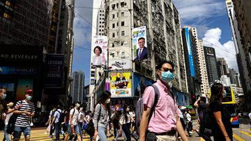 People wearing face masks walk on a downtown street in Hong Kong