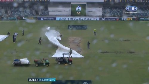The groundsman was working to cover the pitch when a gust blew the covers clear. (9NEWS)