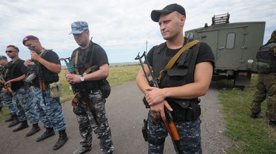 Pro-Russian seperatists stand guard at the site of crash.