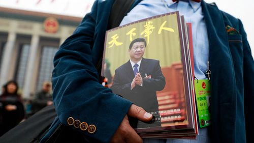 A foreign journalist carrying a magazine with Chinese President Xi Jinping on its front cover. (AAP)