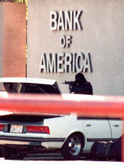 One of the bank robbers fires at LAPD officers with an illegally modified assault rifle.