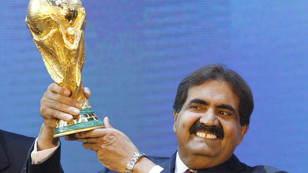 Sheikh Hamad bin Khalifa Al-Thani, Emir of Qatar, holds the World Cup trophy after the announcement of Qatar hosting the 2022 soccer World Cup.(AAP)