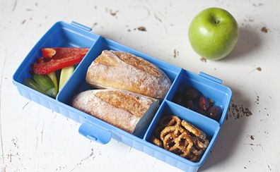 School lunch bread roll with pretzels and vegetable sticks
