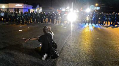 A protester kneels down in front of the police line. (AP)