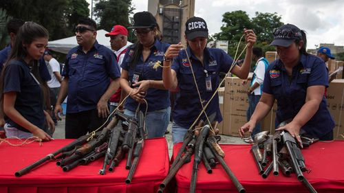 Seized weapons on display in Caracas, Venezuela. (AAP)