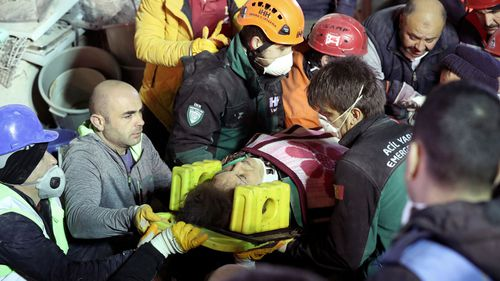 Rescuers carry an injured woman on a stretcher from the site of a collapsed building in Kartal district of Istanbul, Turkey.