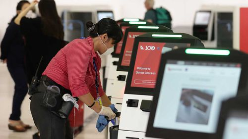 An airport worker cleans a machine at the Qantas check-in area at Sydney Airport.