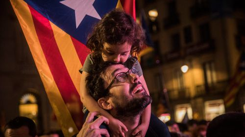 "A child rests on a man's shoulders with a ""estelada"" or pro independence flag in the background. (AP)"
