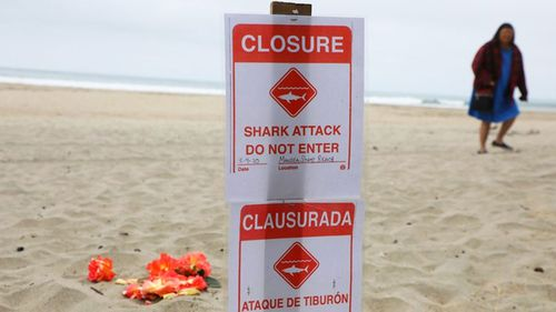 A sign informing visitors the beach is closed due to the shark attack.