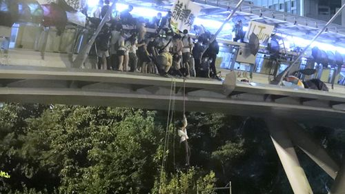 Protesters use a rope to lower themselves from a pedestrian bridge to waiting motorbikes in order to escape from Hong Kong Polytechnic University and the police in Hong Kong.