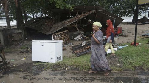 Residents walk past a house damaged by a tsunami, in Carita, Indonesia.