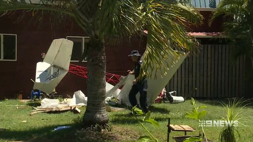 The ultralight aircraft stripped trees of their branches and knocked boards off a Pacific Haven home before crash-landing in the backyard. (9News)