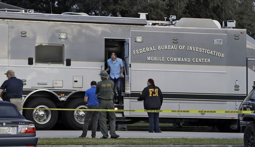 aw enforcement officials climb out a FBI mobile command center vehicle