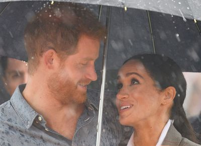 Meghan shields Harry from the rain in Dubbo