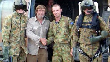 David George flanked by his rescuers.
