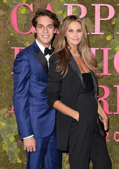 Elle MacPherson andFlynn Busson. Elle wears a Roberto Cavalli suitmade with Italian produced organic wool, produced in accordance with GOTS from organic farming to processing.