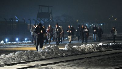 Guests walk by the railway leading to the Birkenau Nazi death camp.