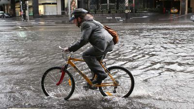 A cyclist rides through floodwaters in Southbank. (AAP)