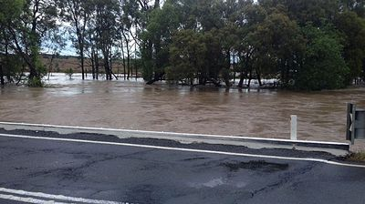 Flood waters come close to covering an entire roadway in Rockhampton .