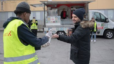 A young volunteer offers hand sanitizer during an information campaign in several different languages about the coronavirus COVID-19 pandemic, in the Tensta suburb of Stockholm, home to a large number of immigrants, on April 12, 2020. Photo: Ali Lorestani