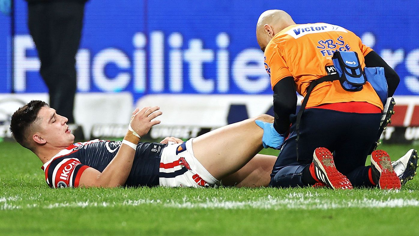 Victor Radley of the Roosters receives attention from the trainer