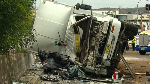 Emergency services had to cut through the nylon sides of the truck before they could access the crushed car. (9NEWS)