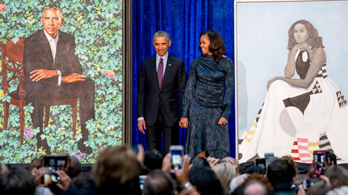 Former President Barack Obama and former first lady Michelle Obama stand on stage together as their official portraits are unveiled. (AP)