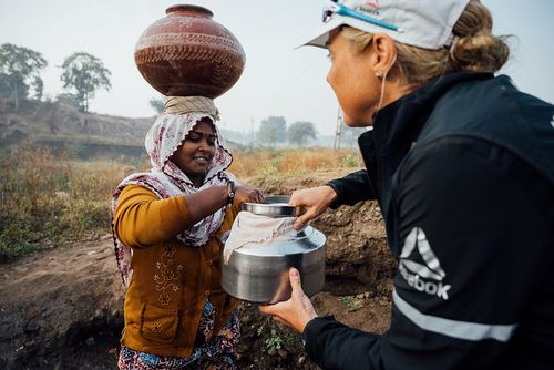 Mina Guli helps a local woman collect water near Dahod,India.