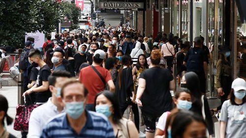Masked pedestrians walk along a Melbourne street.