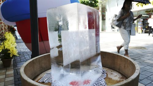 A block of ice is placed at a pedestrian street to cool down the spot in Tokyo. Picture: AAP