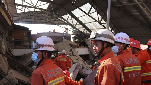 Rescue workers search for victims in the aftermath of the collapse.
