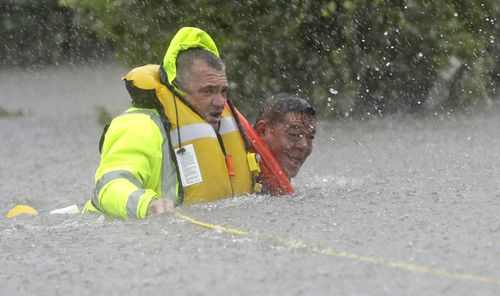Wilford Martinez, right, is rescued from his flooded car by Harris County Sheriff's Department Richard Wagner along Interstate 610 in floodwaters. (AP)