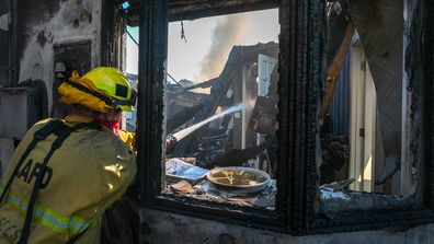 A firefighter hoses down a burning house during the Getty Fire on October 28, 2019 in Los Angeles, California.