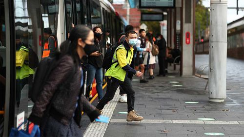 Commuters wearing masks disembark from the light rail at Central Station in Sydney.