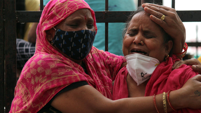 Women mourn the death of a family member, who died due to the coronavirus disease (COVID-19), outside the Lok Nayak Jai Prakash Narayan Hospital (LNJP), one of the largest facilities for coronavirus disease  patients, in New Delhi, India on May 4, 2021. (Photo by Mayank Makhija/NurPhoto via Getty Images)