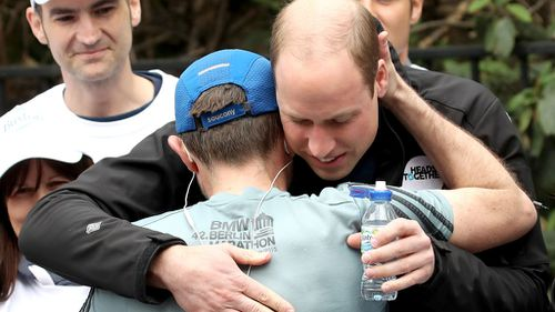 Prince William hugged a runner competing in the London Marathon. (AFP)