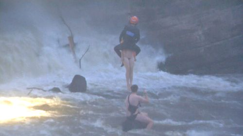 A man and woman who were swimming in the river got swept into the rapids and managed to climb onto a rock