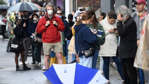 People are seen queuing outside a Centrelink office in Bondi Junction