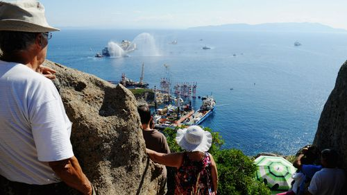 Onlookers watch as the wrecked cruise ship Costa Concordia is towed by tugs from Giglio after being refloated.