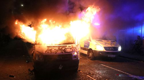 A vandalised police van on fire outside Bridewell Police Station,  as people took part in a protest demonstrating against the Police and Crime Bill.