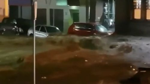 Footage captured cars beings swept away in the floodwaters. (9NEWS)