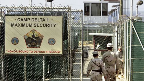In this June 27, 2006, file photo, reviewed by a US Department of Defense official, US military guards walk within Camp Delta military-run prison, at the Guantanamo Bay US Naval Base, Cuba