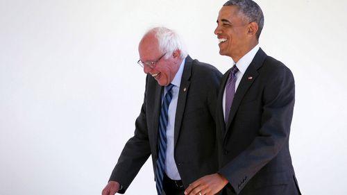Senator Bernie Sanders walks with Barack Obama