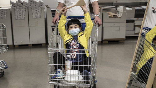 A boy wears a protective mask while sitting in a cart at an IKEA on April 25, 2020 in Wuhan, China.