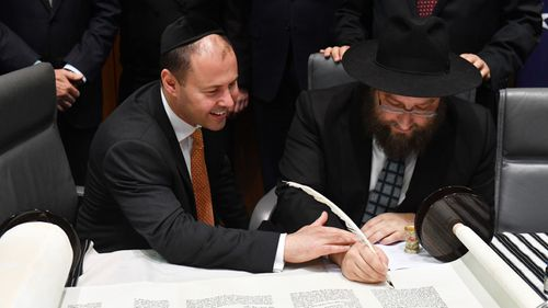Josh Frydenberg and Rabbi Eli Gutnick at a ceremony to mark the completion of the first Torah to be written in Parliament House in Canberra, Thursday, October 19, 2017.