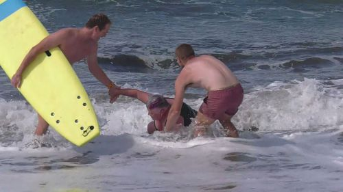 Surfers help Judy to her feet after she became distressed off an Adelaide beach.