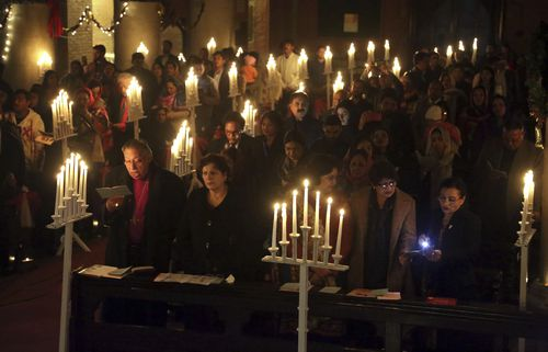Pakistani Christians attend a candlelight service ahead of Christmas at a church in Lahore, Pakistan. (AAP)