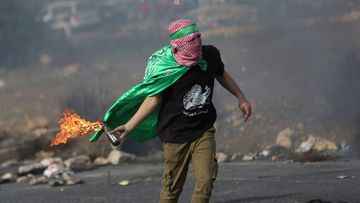 A Palestinian protester throws a molotov cocktail at Israeli soldiers. (AAP)
