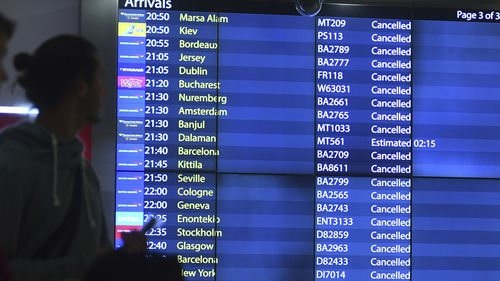 People look at the arrivals board at Gatwick airport, as the airport remains closed after drones were spotted over the airfield.