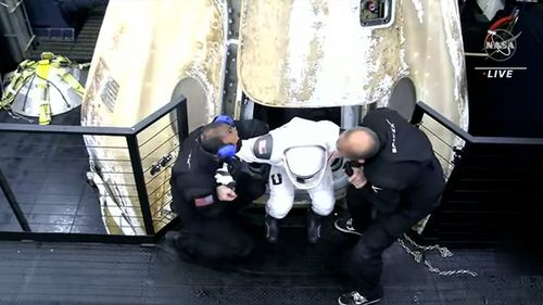 A member of the SpaceX crew is helped out of the Dragon capsule after returning from the International Space Station.